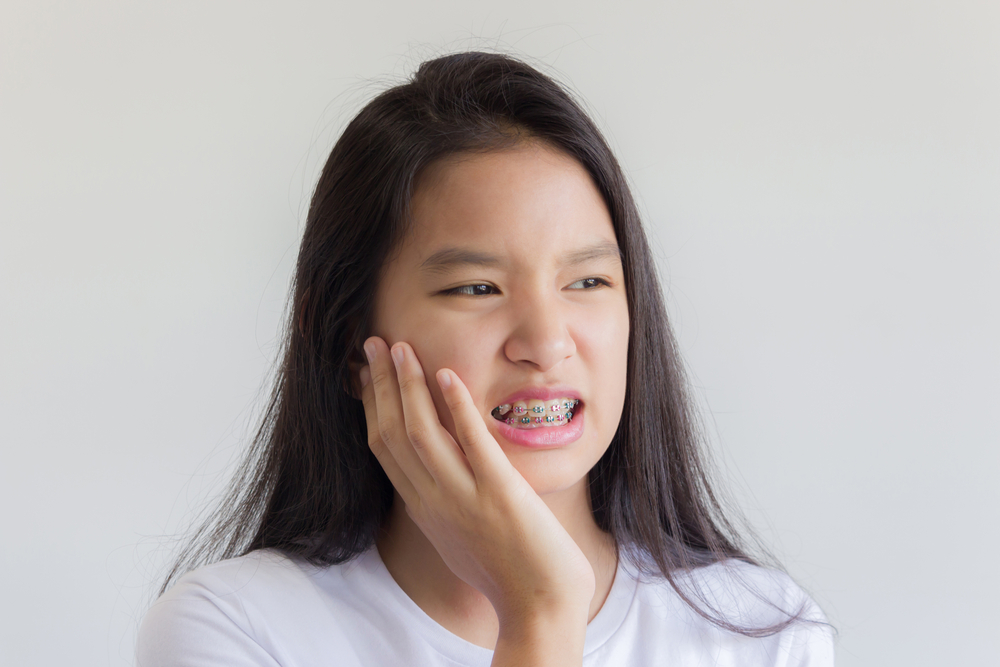 Image of girl wearing braces holding jaw as in they hurt her mouth.
