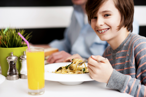 Image of boy wearing braces eating a bowl of pasta.