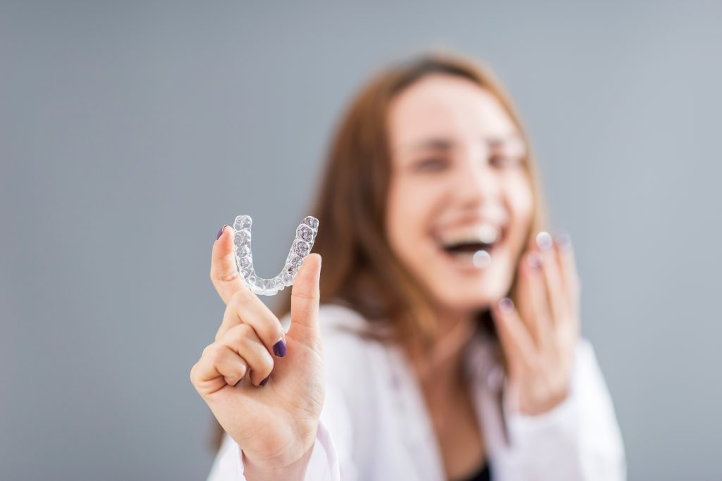 Out of focus woman hold an In-focus Invisalign tray