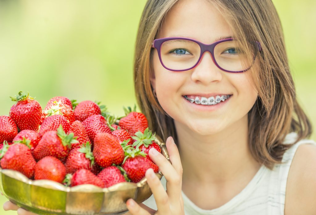 Young girl with glasses and braces hold s bowl of strawberries