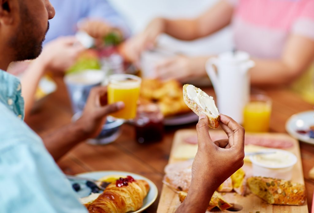 Man eating at a picnic table full of for with friends