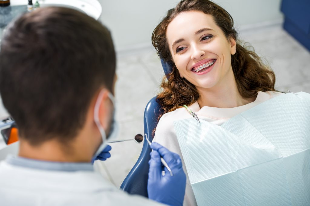 Young woman smiling with braces up at orthodontist