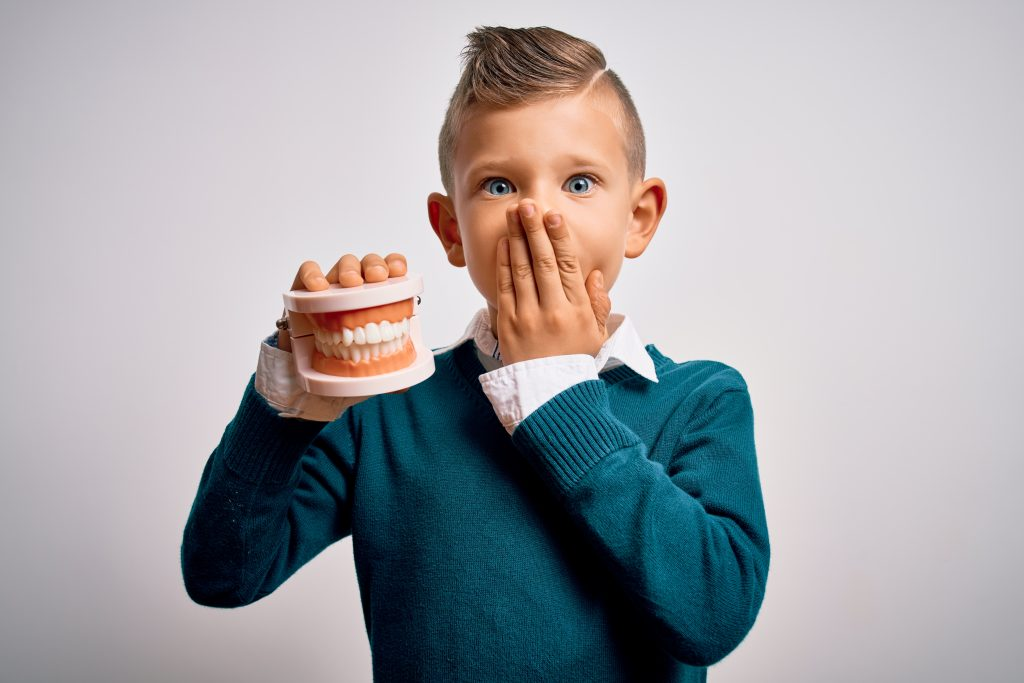 Young boy covering mouth in fear while holding an orthodontists dental mold