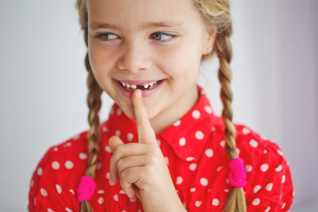 Young girl points to her missing front tooth while smiling