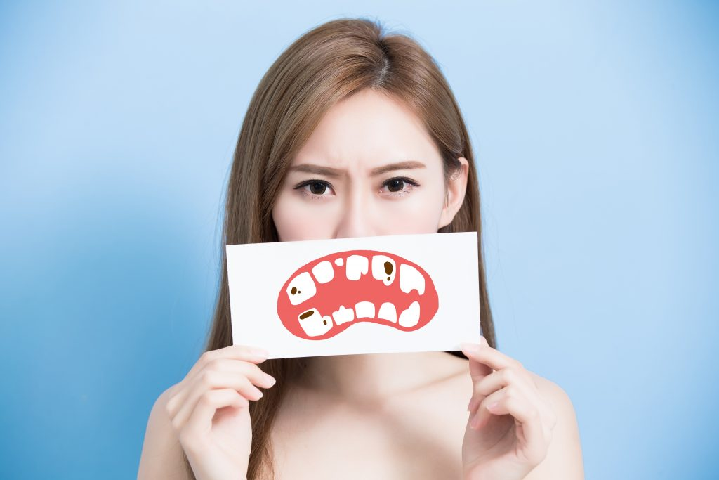 Woman holds a paper cut out of an unhappy mouth featuring teeth with tooth decay in front of her mouth