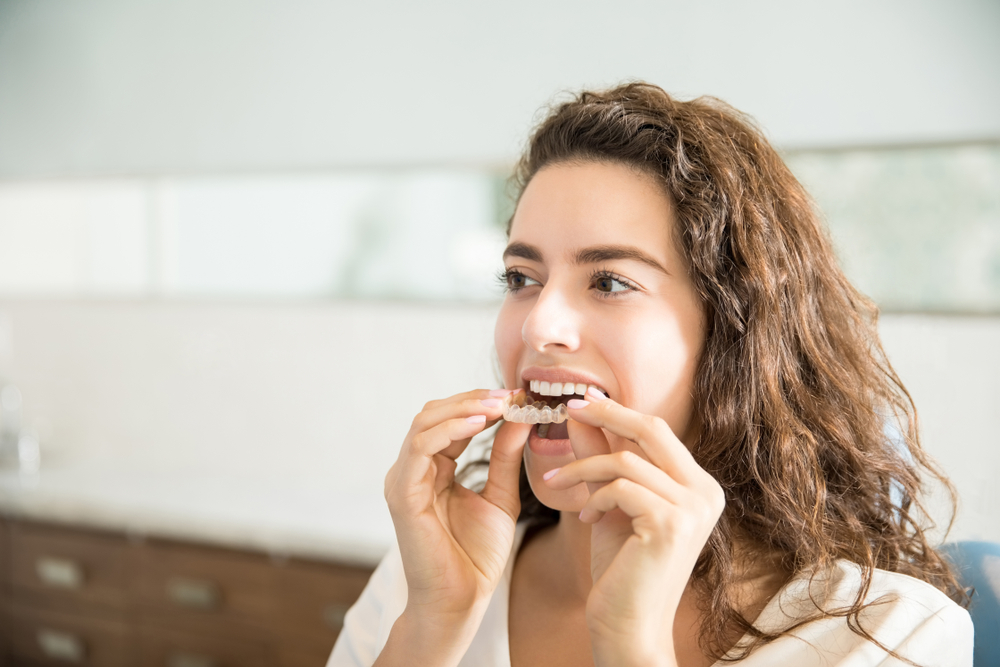 Young woman replaces her clear retainer following braces